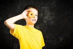 Niño masculino alegre que juega con el buñuelo Fotografía de archivo
