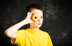 Niño masculino alegre que juega con el buñuelo Imágenes de archivo libres de regalías