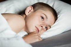 Niño masculino con los ojos abiertos que coloca en la almohada Imagen de archivo