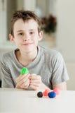 Niño masculino orgulloso que trabaja con la arcilla colorida Foto de archivo libre de regalías