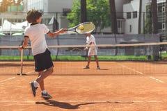 Niño masculino que juega a tenis con el opositor Fotos de archivo libres de regalías