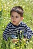 Niño masculino que se pone en cuclillas en un verde Foto de archivo libre de regalías
