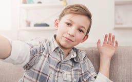 Niño masculino que toma el selfie en el teléfono en casa Fotografía de archivo