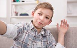 Niño masculino que toma el selfie en el teléfono en casa Imagen de archivo libre de regalías