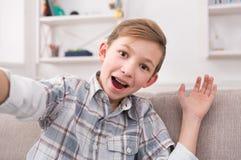 Niño masculino que toma el selfie en el teléfono en casa Imágenes de archivo libres de regalías