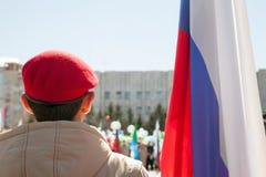 Niño militar que lleva la boina roja al lado de una opinión rusa de la parte posterior de la bandera Imagen de archivo