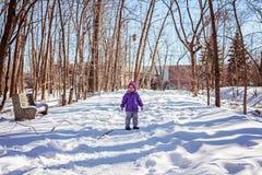 Niño minúsculo solamente en el callejón del parque de la ciudad Tiempo del invierno Fotos de archivo