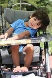 Niño minusválido en cochecito médico Fotos de archivo libres de regalías