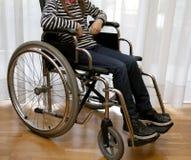 Niño minusválido joven en una silla de ruedas en su dormitorio Imágenes de archivo libres de regalías