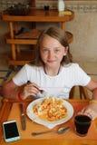 Niño moderno que come el almuerzo con macarrones con la salsa en el restaurante imagen de archivo