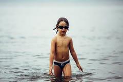 niño Mojado-cabelludo en gafas que camina en el mar imagenes de archivo