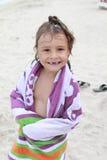 Niño mojado feliz en el mar con la toalla Foto de archivo