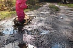 Niño/muchacha con la piscina de agua de la ropa impermeable rosada/el charco de salto fotografía de archivo