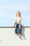 Niño - muchacha que se sienta en el tejado Fotos de archivo