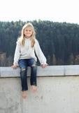 Niño - muchacha que se sienta en la verja Imagen de archivo