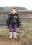 Niño - muchacha que se sienta en un banco Imagen de archivo