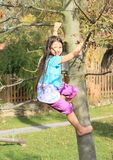 Niño - muchacha que sube en árbol imagenes de archivo