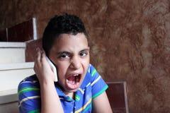 Niño musulmán árabe enojado que habla en teléfono móvil foto de archivo