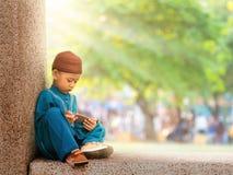 niño musulmán feliz con el vestido lleno que juega el teléfono elegante Imagenes de archivo