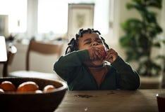 Niño negro que come la fruta foto de archivo