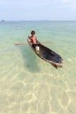Niño no identificado en las canoas en la isla de Mabul Imagen de archivo libre de regalías