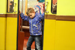 Niño no identificado que intenta cerrar las puertas de un coche de subterráneo Fotos de archivo libres de regalías