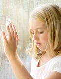 Niño o adolescente en una ventana Imagen de archivo libre de regalías