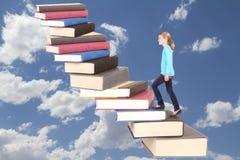 Niño o adolescente subiendo una caja de la escalera de libros Imagenes de archivo