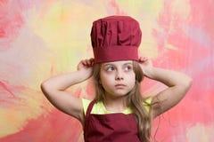 Niño o bebé en el sombrero del cocinero o del cocinero, delantal Fotos de archivo