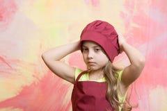 Niño o bebé en el sombrero del cocinero o del cocinero, delantal Foto de archivo
