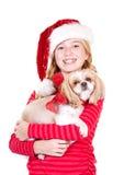 Niño o tenencia adolescente un perro que lleva un sombrero de Papá Noel Fotos de archivo