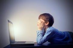 Niño observando la computadora portátil Imágenes de archivo libres de regalías