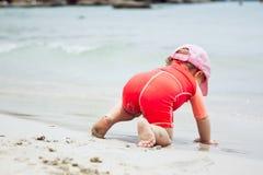 Niño obstinado que se arrastra hacia el agua en la playa durante vacaciones de verano fotografía de archivo