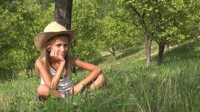 Niño pensativo que se relaja en hierba en yarda, muchacha pensativa en el jardín, verano 4K