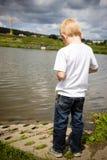 Niño pensativo solo que piensa por el río soledad Fotos de archivo