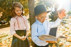 Niño pequeño 6, 7 años con el sombrero, vidrios, leyendo un libro y a una muchacha 7, 8 años, junto en el parque soleado del otoñ fotografía de archivo libre de regalías