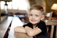 Niño pequeño 4-5 años que se sientan en la tabla de madera en café Fotografía de archivo