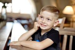Niño pequeño 4-5 años que se sientan en la tabla de madera en café Fotografía de archivo libre de regalías