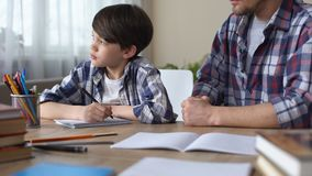 Niño pequeño aburrido que hace la preparación con el padre estricto, niño triste que mira en ventana almacen de video