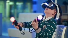 Niño pequeño activo que disfruta de realidad virtual con los reguladores del movimiento en sus manos almacen de metraje de vídeo
