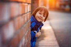 Niño pequeño adorable, al lado de la pared de ladrillo, comiendo la barra de chocolate encendido Foto de archivo