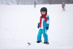 Niño pequeño adorable con la chaqueta azul y un casco, esquiando Imagenes de archivo