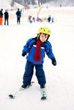 Niño pequeño adorable con la chaqueta azul y un casco, esquiando Imagen de archivo libre de regalías