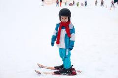 Niño pequeño adorable con la chaqueta azul y un casco, esquiando Fotografía de archivo libre de regalías