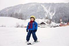 Niño pequeño adorable con la chaqueta azul y un casco, esquiando Fotos de archivo
