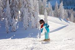 Niño pequeño adorable con la chaqueta azul y un casco, esquiando Imagen de archivo