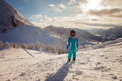 Niño pequeño adorable con la chaqueta azul y un casco, esquiando Fotografía de archivo