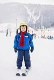 Niño pequeño adorable con la chaqueta azul y un casco, esquiando Fotos de archivo libres de regalías