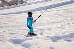 Niño pequeño adorable con la chaqueta azul y un casco, esquiando Foto de archivo