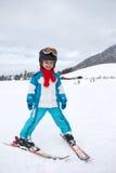 Niño pequeño adorable con la chaqueta azul y un casco, esquiando Imágenes de archivo libres de regalías